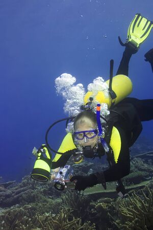 Diver with camera in deep and bubbles. Imagens