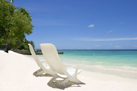 Two empty beach chairs. Coast of Indian ocean. Maldives photo