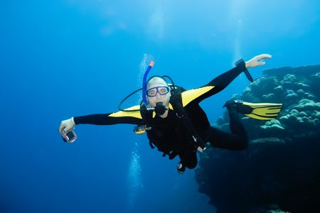boldness: Diver flying underwater with camera. Stock Photo