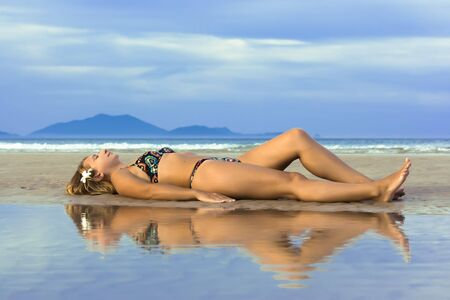 Reflection of Young woman with plumeria flower on the tropical beach. photo
