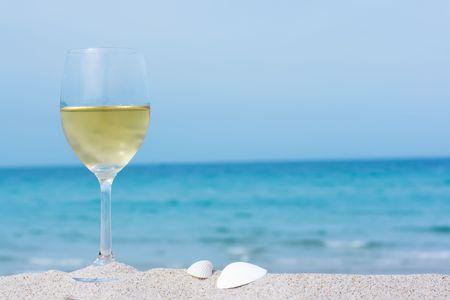 Bicchiere di vino bianco sulla spiaggia tropicale