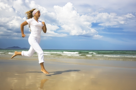 Young woman is running near the ocean. Space for copy photo