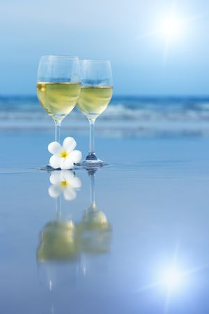 plumeria on a white background: Reflection of two glasses of white wine on tropical beach