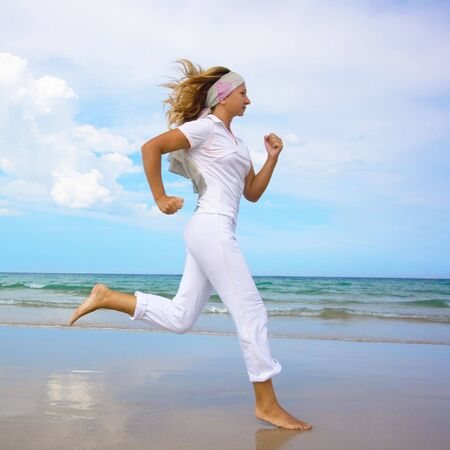 Young woman running near the ocean. Space for copy