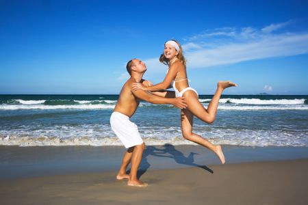 Young couple have a fun time on the tropical beach.  photo