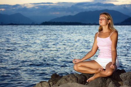 Young woman meditating at sunset time near ocean photo