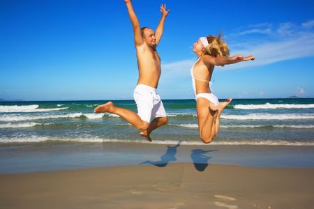 Young couple jumping on the tropical beach. photo