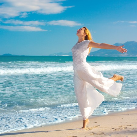 woman dancing: Young woman dancing near the ocean
