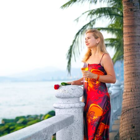 Young woman with glass of white wine in red dress near the ocean photo