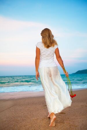 Young fashion woman walking with flowers on the  beach
