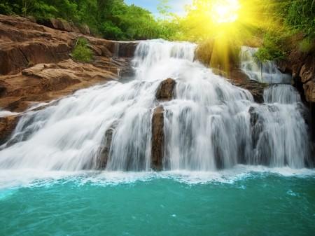 Cascada de la piscina en la selva tropical y la luz solar Foto de archivo
