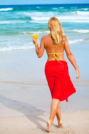 Woman with juice on the tropical beach photo