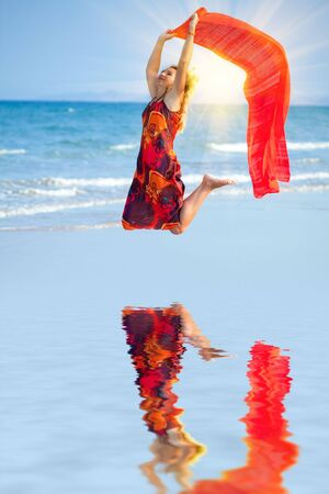 tine: Woman jumping with red sarong at sunset tine