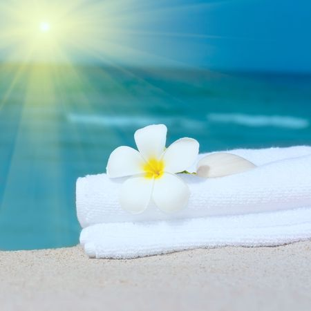 Towel and plumeria lower on the tropical beach photo