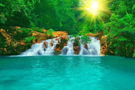 Waterfall in tropical forest at sunny day Stock Photo