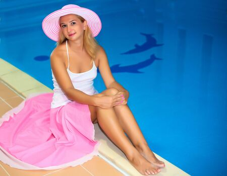 Woman in pink clothes near the swiming pool photo