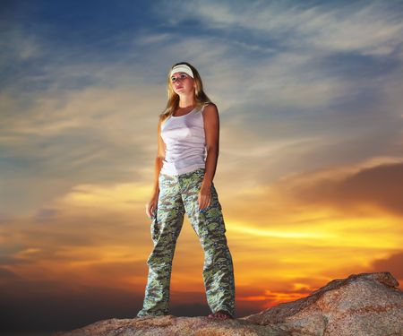 Military woman staying aon the mountain peak at sunrise time photo