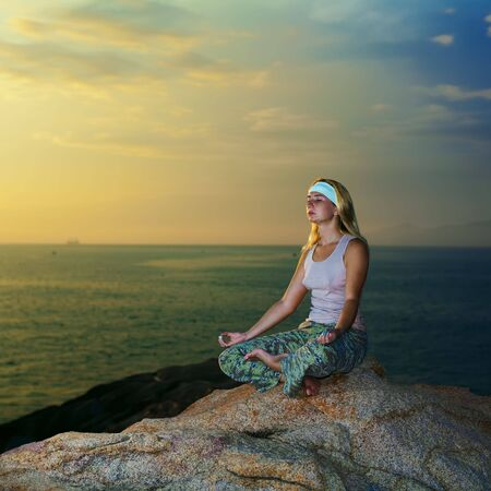 Young woman meditating at sunset time near ocean Stock Photo - 4794324