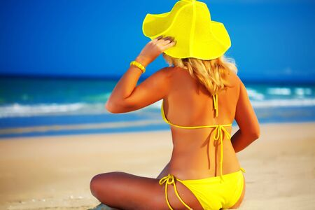 Woman in yellow hat sitting on the beach Stock Photo