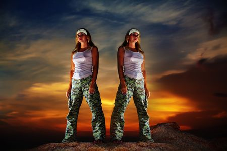 aon: Two military woman staying aon the mountain peak at sunrise time