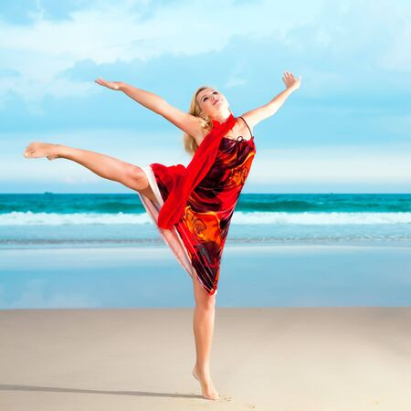 Woman dancing near the ocean in red clothes photo