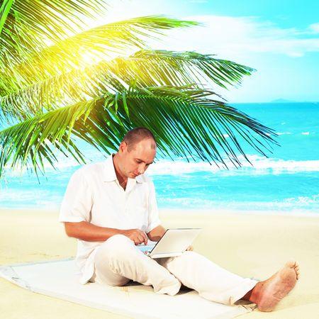 netbook: Man with netbook working near the ocean under palmtree.