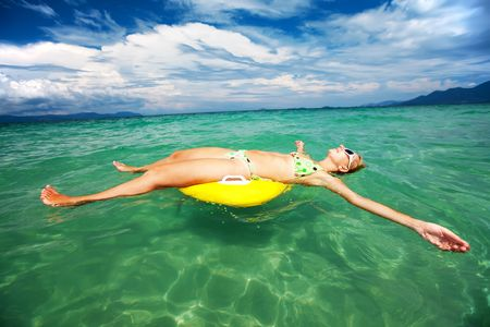 Woman relaxing with life buoy in the ocean photo