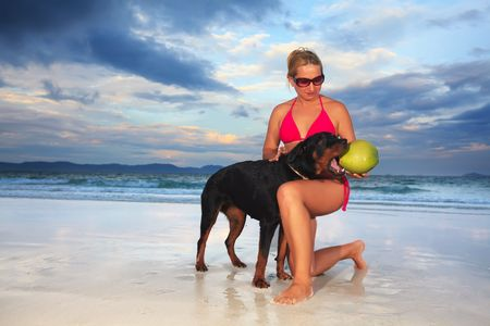 Woman playing with dog near the ocean at sunset time photo