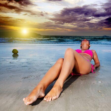 Young woman in bikini near the ocean photo
