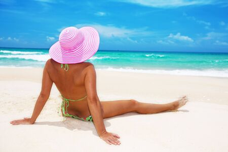 Woman in pink hat sunbathing on the beach photo