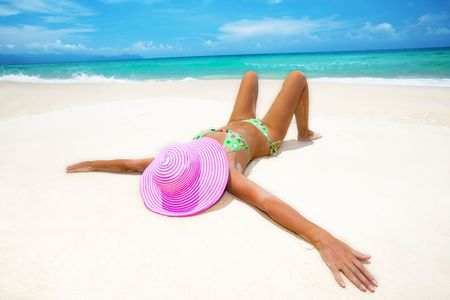 pink hat: Woman in pink hat lies on the beach Stock Photo