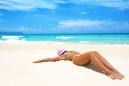 Woman in pink hat lies on the beach Stock Photo - 4948711