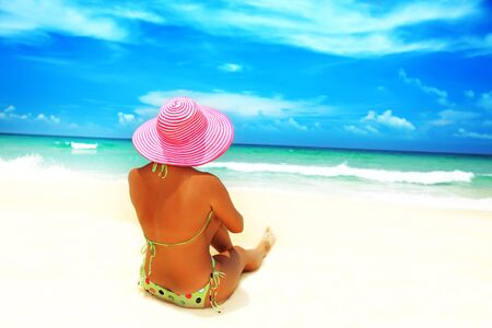 Woman in pink hat sunbathing on the beach Stock Photo - 4982890