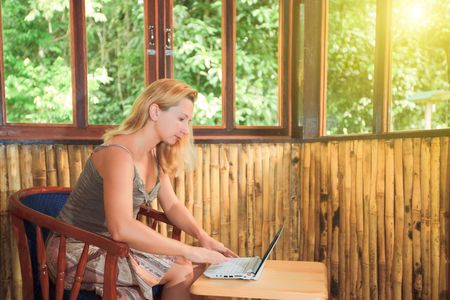 bamboo house: Young woman with laptop in bamboo house Stock Photo
