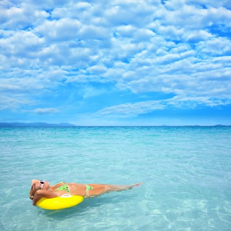 Woman relaxing on the tube in clean blue ocean photo
