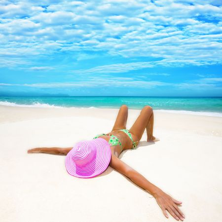 untruth: Woman in pink hat lies on the beach Stock Photo