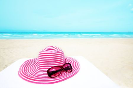 pink hat: Pink hat and sunglasses near the ocean Stock Photo