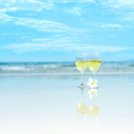 热带海滩上两杯白葡萄酒的倒影