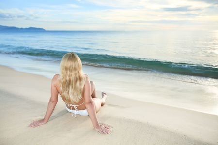 Woman sitting near the ocean at sunrise time photo