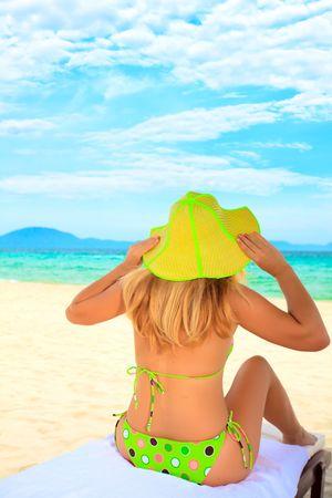 Junge Frau zum Sonnenbaden auf den Stuhl in der Nähe des Ozeans Standard-Bild