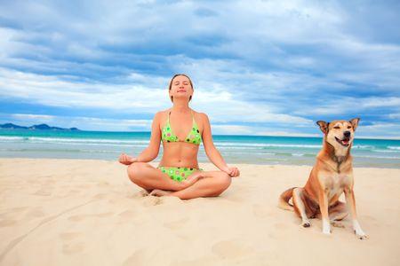 mujer perro: Mujer con perro est� meditando en la playa tropical