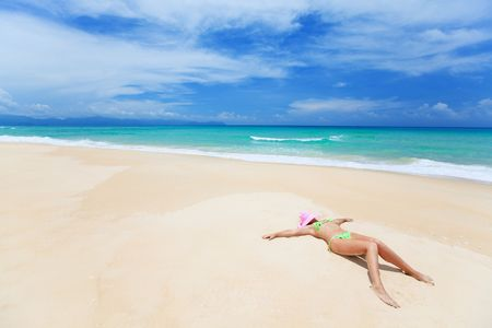 Woman in pink hat lies on the beach Stock Photo - 5508114