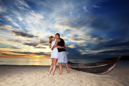 Couple kissing at sunset time on romantic tropical beach photo