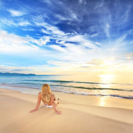 Woman sunbathing on the beach at sunrise time photo