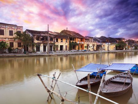 hoi an: View on the old town of Hoi An from the river. Boats in the foreground. Stock Photo