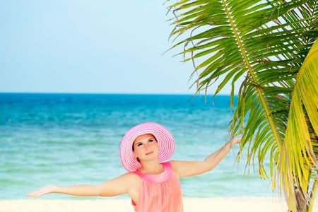 Beautiful woman in pink hat on the beach. Space for copy photo