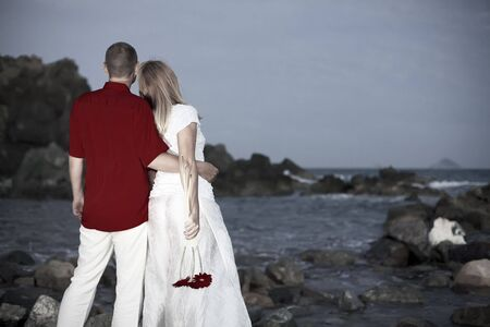 Young couple near the ocean with flowers at night Stock Photo - 5724429