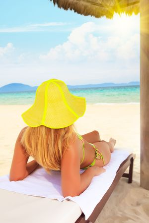 Young woman sunbathing on the chair near the ocean photo