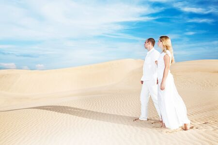 Young couple walking on desert dune in white clothes photo