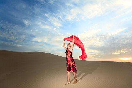 Beautiful woman with red showl in desert